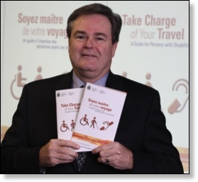 The Agency's Chair and CEO holds up copies of Take Charge of Your Travel